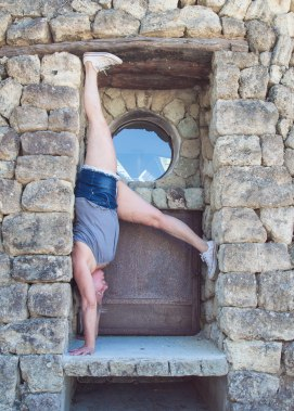 Ady doing a handstand by a window